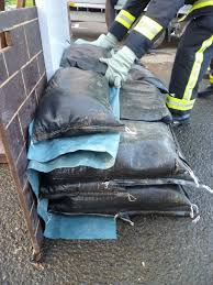 sandbag wall demonstration showing firefighter layering polythene sheeting with sandbags