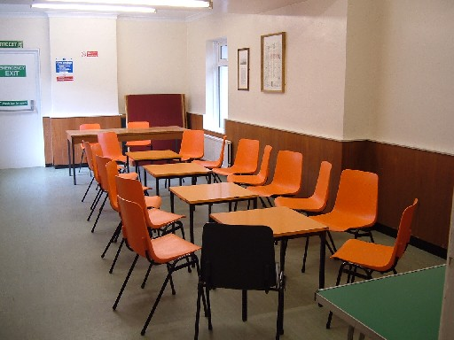The Committee Room, tables and orange chairs in meeting room